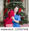 Young girl pulling out red jacket from gift bag with Christmas tree in background - stock photo