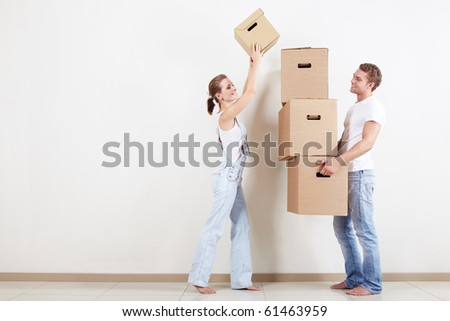 Young girl puts a cardboard box on the other - stock photo