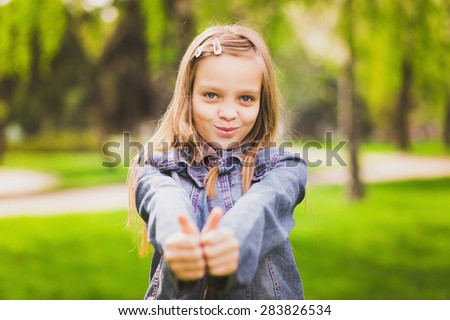Young girl puts her big thumbs up. Portrait of cheerful kid. Smiling girl having fun outside. Happy successful person. - stock photo