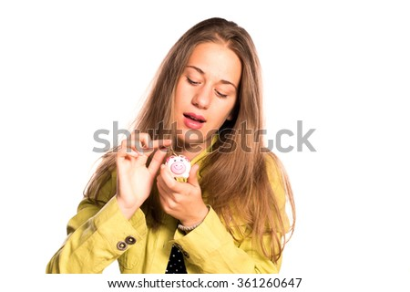 Young girl putting coin in small piggy bank