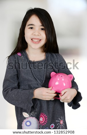 Young girl putting money in her piggy bank