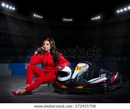 Young girl racer with kart at stadium - stock photo