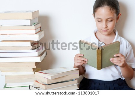 Young girl reading a book at home, surrounded by piles of books.