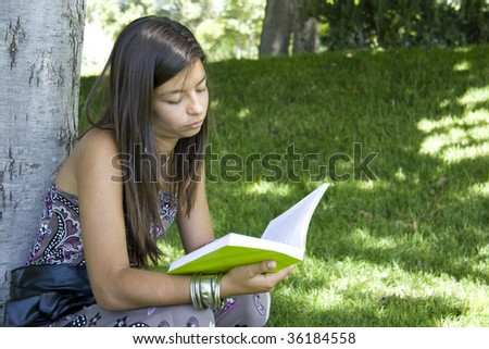 Young girl reading a book at the park
