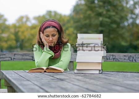 Young girl reading a book in a park - stock photo