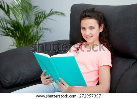 Young girl reading a book on the sofa at home