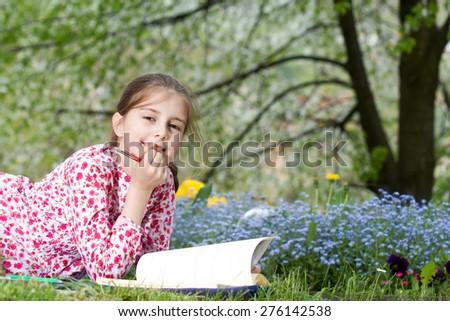 Young girl reading a book outdoor - stock photo