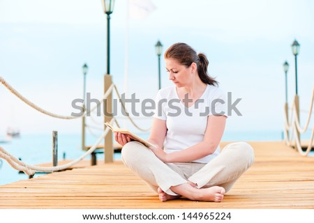 Young girl reading a book while sitting on a pier barefoot - stock photo