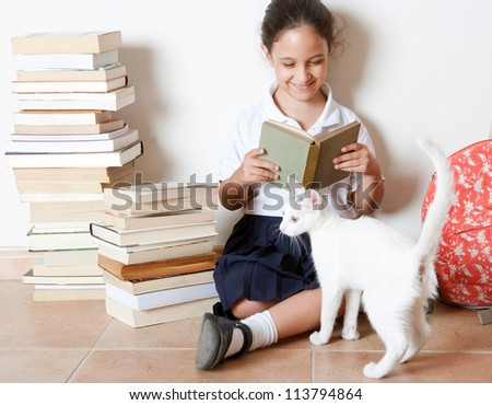 Young girl reading a book with her cat at home, sitting next to two piles of books. - stock photo
