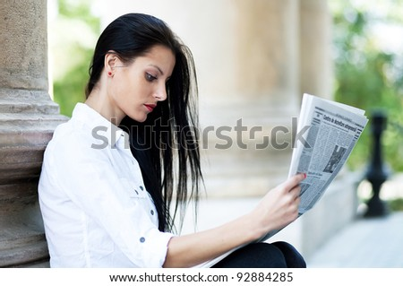 Young girl reading a newspaper - stock photo