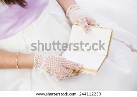 Young girl reading a prayer book with blank copy space in her First Holy Communion - stock photo