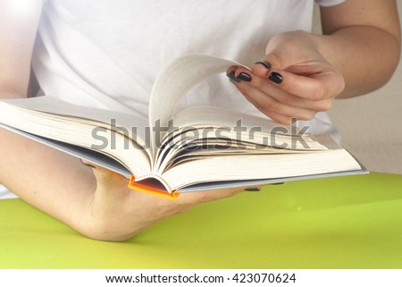 Young girl reading an  open book  old book. Knowledge, Science. Back to school. Copy space. Toned image.