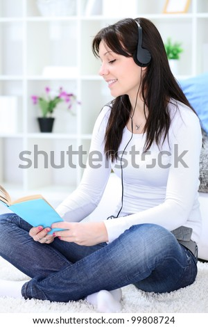Young girl reading book and listening music, enjoying time - stock photo