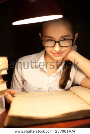 Young girl reading book under lamp in the dark
