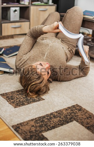 Young girl reading book while laying on the floor in the living room.