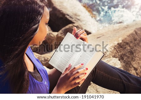 Young girl reading her Bible by the sea - stock photo