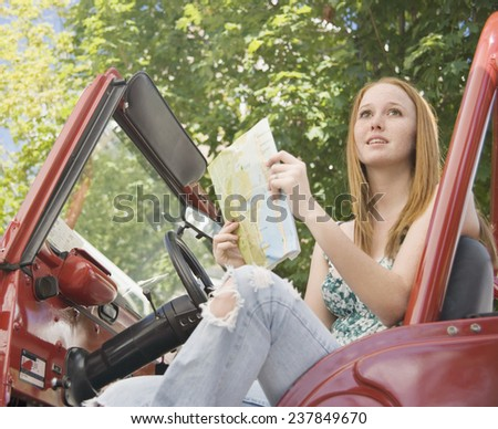 Young Girl Reading Map in Car - stock photo