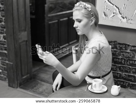 Young girl reading messages on smart phone - black and white photo.