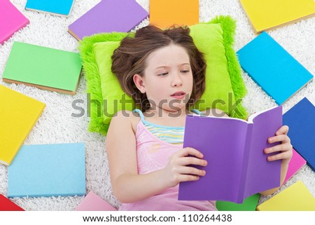 Young girl reading - surrounded by lots of colorful books - stock photo