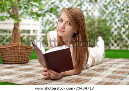 Young girl reads a book in the garden