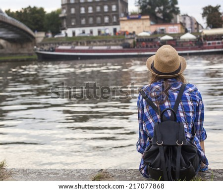 Young girl (rear view) sits on the bank of Vistula River in Krakow. European Tour. - stock photo