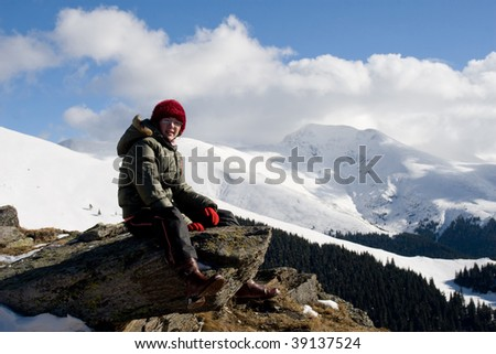Young girl relaxing in the winter sun near mountain peaks