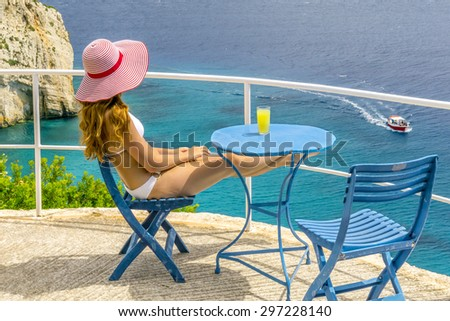 Young girl relaxing with drink and watching trip boats, Greek islands - stock photo