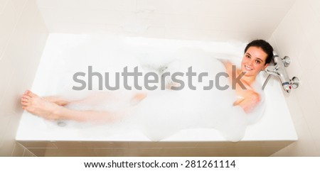 Young girl relaxing with foam in bath