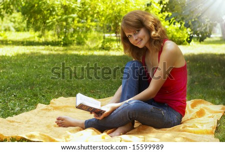 young girl reposes in park with book - stock photo