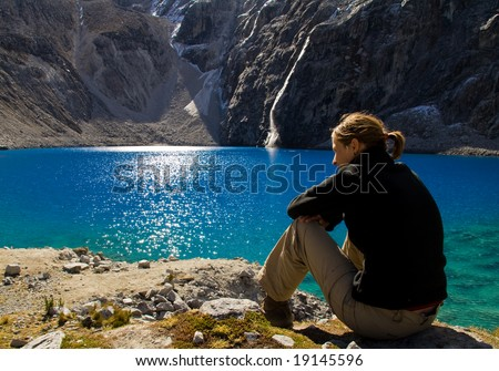 young girl resting at an amazing blue mountain lake