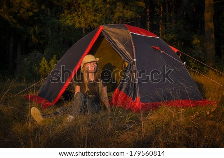 young girl rests near the camp tent in forest - stock photo