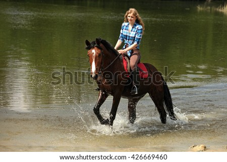 Young girl riding a big brown horse through water