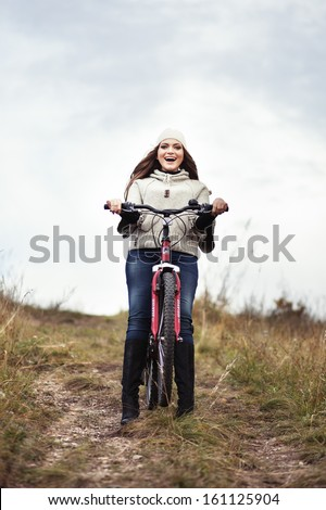 Young girl riding a mountain bike and laughing. - stock photo
