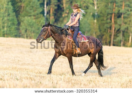 Young girl riding black horse - stock photo