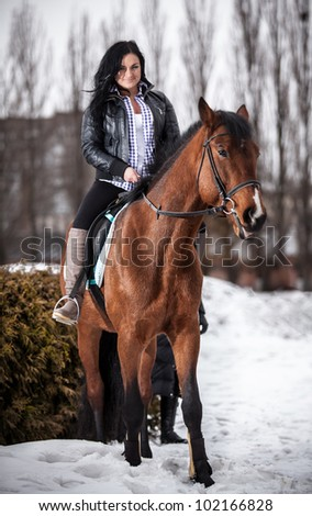 Young girl riding horse on hippodrome - stock photo