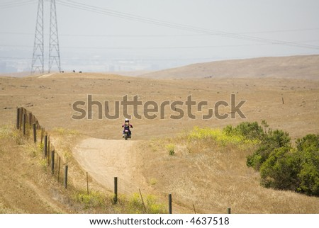 Young girl riding motorbike alone on an isolated trail