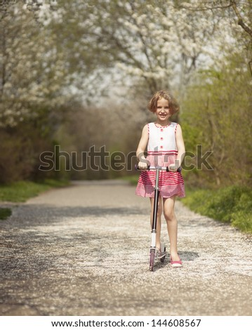 Young girl riding scooter on path through park