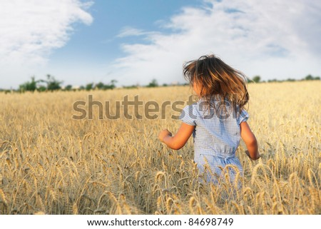 young girl running in yellow field - stock photo