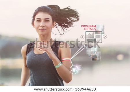 Young girl running on a beach during morning with wearable devices - stock photo