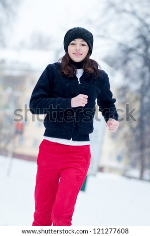 Young girl running on a cold winter day outdoor - stock photo