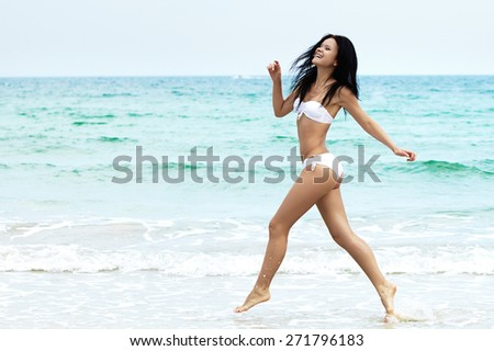 Young girl running on beach. Athletic happy woman jogging in white bikini enjoying the sun exercising. Healthy lifestyle. Fun walk along the shore. Perfect fitness body shapes and tan skin