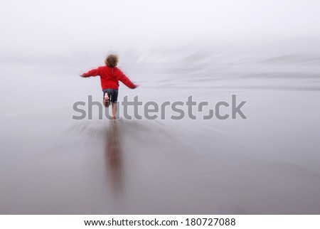 Young girl running on beach looking at ocean zoomed blur - stock photo