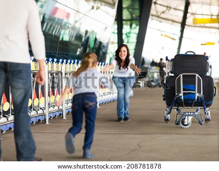 young girl running to her mother at airport after a long wait with her father - stock photo
