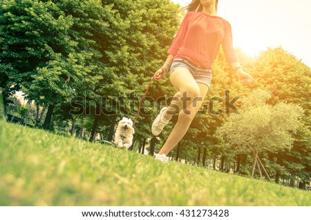 Young girl running with her dog. Puppy white dog is running with it's owner. Concept about friendship, animal and freedom - stock photo