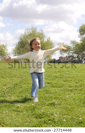 Young girl running with open arms at park