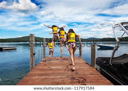 Young girl runs down the dock to jump to a warm summer lake - stock photo