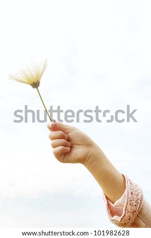 Young girl's arm held up in the air, holding a white daisy against the sky. - stock photo