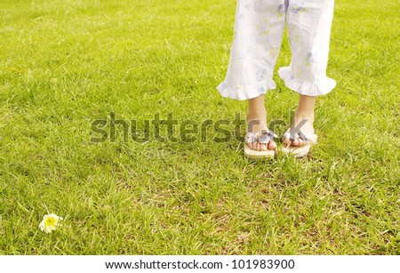 Young girl's feet wearing summer sandals and standing on bright green grass in the park. - stock photo