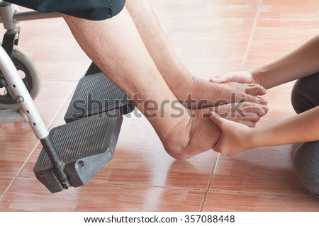 Young girl's foot touches and holds an old woman's wrinkled foot. - stock photo