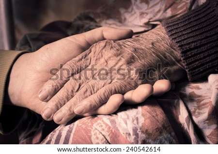 Young girl's hand touches and holds an old woman's wrinkled hand - stock photo